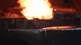 Ferreiro que bate a barra de metal quente com o martelo maciço no batente no movimento lento video estoque