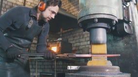 Ferreiro que forja o ferro encarnado no batente - martelamento automático imagem de stock
