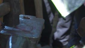 Ferreiro que forja o metal derretido no batente na forja filme