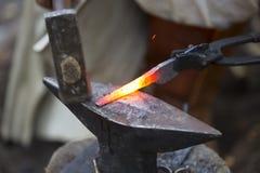 Ferreiro que martela a seta quente do metal Foto de Stock