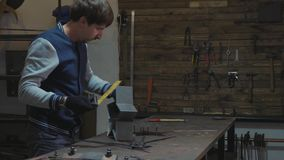Ferreiro que trabalha com detalhe decorativo do metal em sua oficina filme
