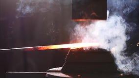 Ferreiro que usa a máquina de martelo para dar forma ao metal quente vazio na oficina da forja video estoque