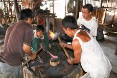 Ferreiros durante a batida do ferro no lago Inle fotografia de stock