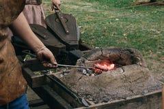 Ferreiros que picam carvões ardentes na fornalha e que espremem foles para inflamar o fogo foto de stock royalty free