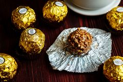 2019-02-05 Ferrero Rocher, μικρά πακέτα πρόχειρων φαγητών σοκολάτας πολυτέλειας μεγέθους στον ξύλινο πίνακα για χαλαρώνει το χρόν στοκ εικόνες