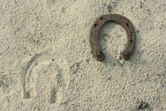 Ferri di cavallo arrugginiti su un fondo della sabbia - scena rustica in uno stile country Vecchio ferro di cavallo del ferro - s Fotografia Stock