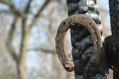 Ferri di cavallo arrugginiti su un palo di legno bruciato - scena rustica in uno stile country Immagini Stock Libere da Diritti