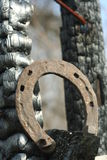 Ferri di cavallo arrugginiti su un palo di legno bruciato - scena rustica in uno stile country immagini stock