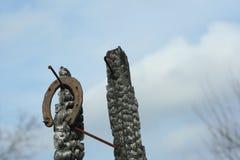 Ferri di cavallo arrugginiti su un palo di legno bruciato - scena rustica in uno stile country Fotografia Stock Libera da Diritti