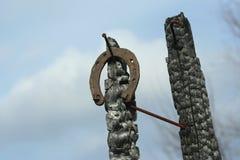 Ferri di cavallo arrugginiti su un palo di legno bruciato - scena rustica in uno stile country Immagine Stock Libera da Diritti