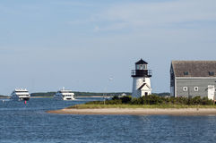Ferries Pass By Lighthouse on Cape Cod. Two ferries pass by Hyannis Harbor lighthouse on a summer day in Cape Cod, Massachusetts Royalty Free Stock Images