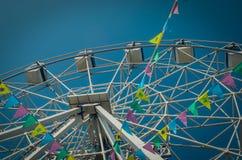 Ferris koło i kolorowe flagi w parku rozrywkim przeciw th fotografia stock