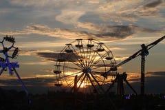 Ferris roulent dedans le coucher du soleil Images stock
