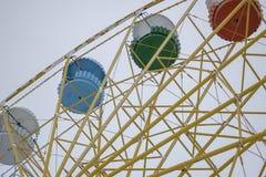 Ferris rueda-amarillo con las cabinas multicoloras Imagenes de archivo