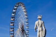 Ferris spinge dentro il cielo blu profondo con una statua accanto Fotografia Stock Libera da Diritti