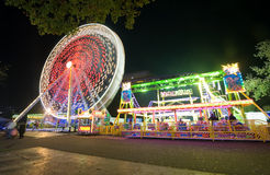 Ferris wheel. A ferris wheel and a little rollercoaster in the evening at an amusement park Royalty Free Stock Images