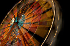 Ferris Wheel. Wide-angle shot of a ferris wheel in motion at night causing light trail motion blur Stock Photography