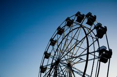 Ferris wheel. In evening silhouetted against sky with copy space on the left Stock Images