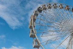 Ferris wheel against blue sky as background. Big ferris wheel against blue sky wiht clouds from below. Emty Stock Photography