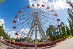 Ferris wheel against blue sky background in city park Stock Images