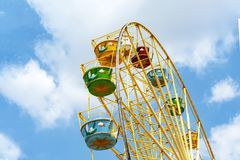 Ferris wheel with colorful colorful booths in the amusement Park the blue sky.