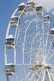 Ferris wheel against the blue sky. Fragment of a white ferris wheel against a blue sky background Royalty Free Stock Photo