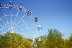 Ferris wheel against the blue sky and trees.  Stock Photo