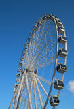 Ferris wheel against bright blue sky Stock Images