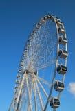 Ferris wheel against bright blue sky. Ferris wheel brightly lit with the sun against blue sky Stock Images