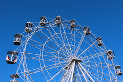 Ferris wheel against bright blue sky Stock Photo