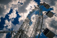Ferris wheel against cloudy blue sky Stock Images