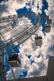 Ferris wheel against cloudy blue sky Stock Photo