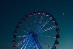 Ferris wheel against dark evening sky. Inactive ferris wheel against dark evening sky with half moon Royalty Free Stock Image