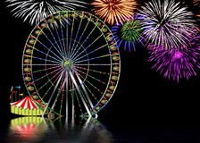 Ferris Wheel at Amusement Park Baclground. Night-time image of large ferris wheel in amusement park with fireworks in the background.  Reflections in water Stock Photo