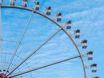 Ferris wheel at an amusement park. Offering fun rides in passenger gondolas against a blue sky, partial view Stock Photo