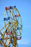 Ferris Wheel Amusement Ride Against Blue Sky. View from below of top section of a double ferris wheel against blue sky background Stock Photos