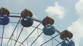 Ferris Wheel av ljus färg på bakgrund för blå himmel med vita moln Arkivfoton