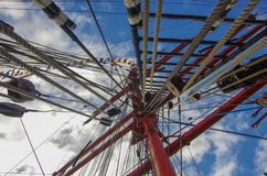 Ferris wheel on background of blue sky. Masts of a sailing vessel strung with ropes against a blue sky stock photos