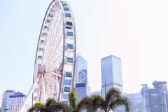 Ferris wheel on a background of blue sky and skyscrapers. Skyline. Stock Photos