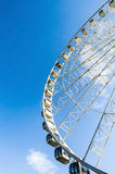 Ferris wheel on the background of blue sky. A ferris wheel viewed from the bottom half Royalty Free Stock Images