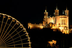 Ferris wheel and basilica. The basilica (Lyon - France) was started in 1872 and was designed by Pierre Bossan and Sainte-Marie-Pierre. The building was erected Royalty Free Stock Photo