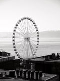 Ferris wheel behind city roofs in Seattle.  Royalty Free Stock Images