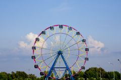 Ferris wheel  big wheel on the background of bright blue sky background. Background field of the mobile screen cloud wheel with cabins yellow pink flowers Royalty Free Stock Image