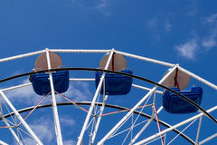 Ferris wheel with blue bowls against blue sky with thin clouds Royalty Free Stock Photos