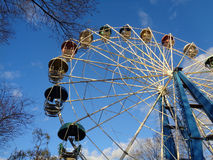 Ferris Wheel and blue sky. Ferris Wheel in the city park, blue sky and trees, winter season Royalty Free Stock Photography