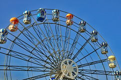 Ferris wheel soaring into blue sky Stock Image