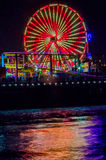 Ferris Wheel and Boardwalk At Night. Giant ferris wheel with bright red and white lights Stock Photos
