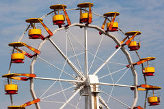 Ferris wheel with bright colored cabins in amusement park. Ferris wheel with bright colored cabins in amusement park against blue sky and white clouds Stock Photos