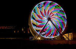 Ferris Wheel with Bright Lights. A ferris wheel is lite up with bright lights as it turns Royalty Free Stock Photo