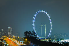 Ferris wheel and buildings seen from Singapore at night. Stock Photo